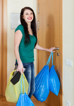 Happy brunette woman putting out the garbage at home photo