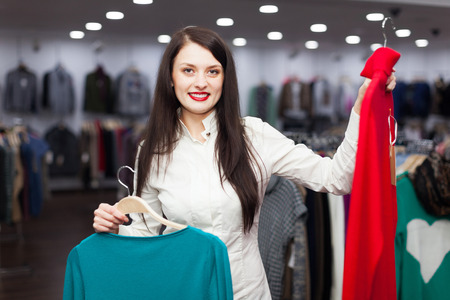 'pull over': Joyful female buyer with two sweaters at clothing store