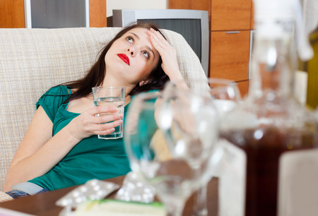Suffering woman with glass of water