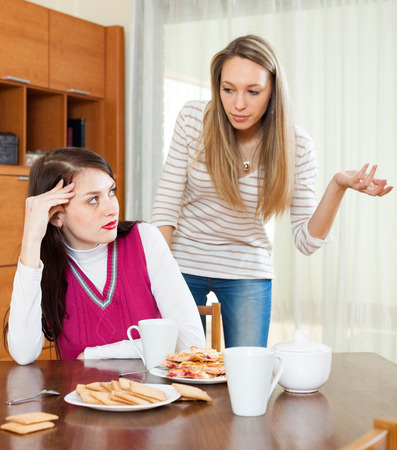 contend: Two sad girls having conflict at table in home