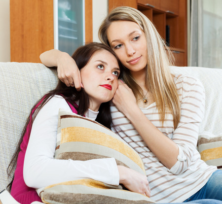 appease: crying woman has problem, other woman  consoling her at sofa in home