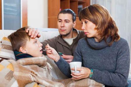 Loving parents giving pills to son at home Stock Photo