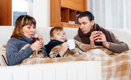 freezing parents and teenage son with cups of tea warming near warm calorifer in home