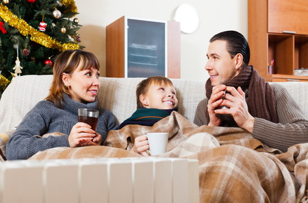 Happy family with teen with radiator and Christmas tree at home