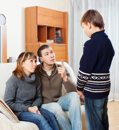 fracas: serious mother and father together scolding teenager son at home