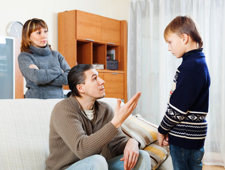 fracas: ordinary parents berating teenager son in living room at home Stock Photo