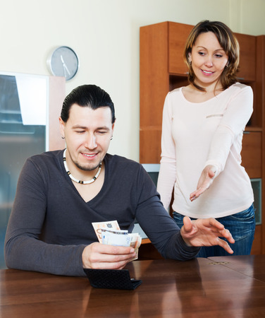 rapacity: Financial problems in family. Man counting money, wife watching him in home