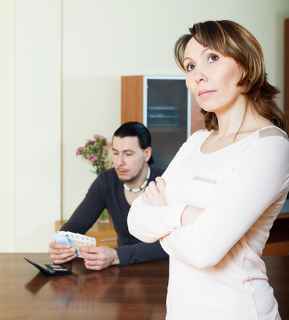 rapacity: Financial problems in the family. Sad woman against man with money Stock Photo