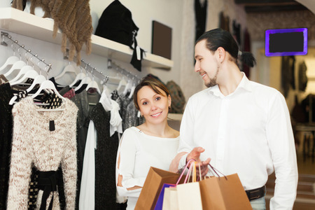 cheerful couple with shopping bags at clothing shop photo