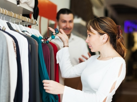 Man and woman choosing clothes at clothing boutique photo