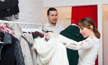 choosing clothes: Smiling adult couple choosing clothes at clothing shop