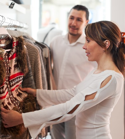 choosing clothes: Smiling couple choosing clothes at clothing shop Stock Photo