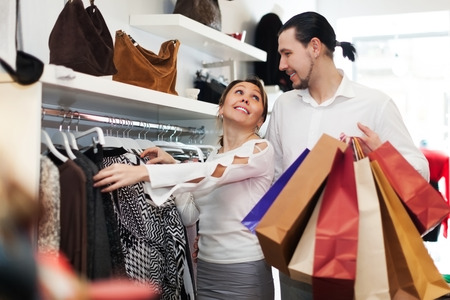 Young couple choosing clothes at clothing store together photo
