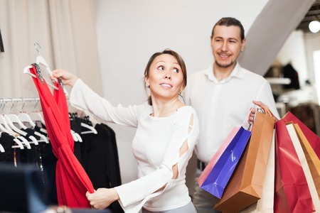 choosing clothes: Happy couple choosing clothes at boutique Stock Photo