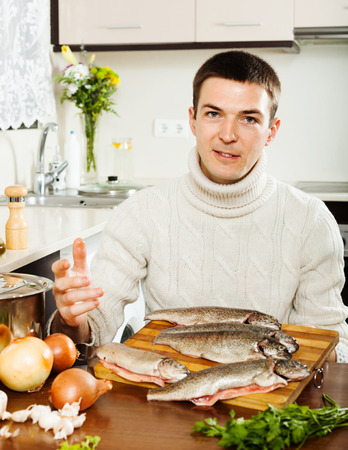 brook trout: Handsome man cooking trout fish  in home kitchen Stock Photo