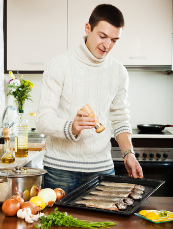 cheeful: man adding spices in raw fish on roasting pan Stock Photo
