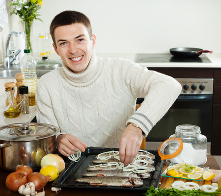 brook trout: Happy man cooking raw fish with lemon and onion