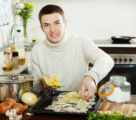 girdle: Handsome guy cooking trout fish with lemon in roasting pan