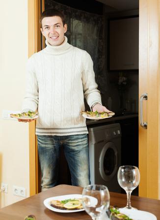 pesce cotto: Uomo sorridente che serve cucinato pesce sulla tavola con la famiglia a casa