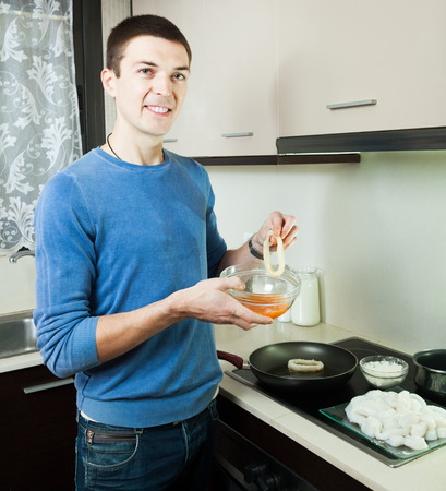 calmar: Smiling guy frying  calamary in batter at kitchen Stock Photo