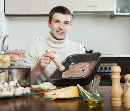 roasting pan: Handsome man cooking  meat . Adding raw meat in roasting pan
