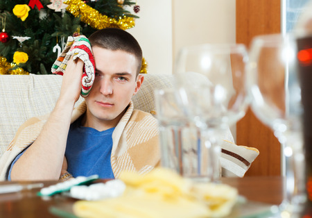 hangover: Man having hangover during christmas holidays at home Stock Photo