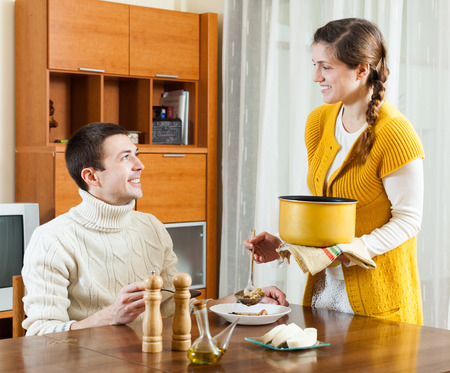 beloved: Ordinary girl serving lunch loving guy at table Stock Photo