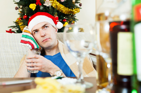 hangover: Suffering guy with hangover sitting at table in Santa hat with glass of water