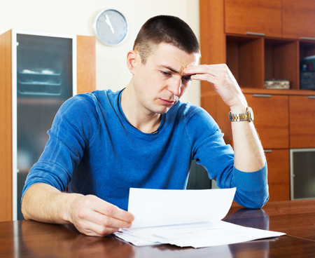 composed: Upset puzzled guy looking at document sitting by table Stock Photo