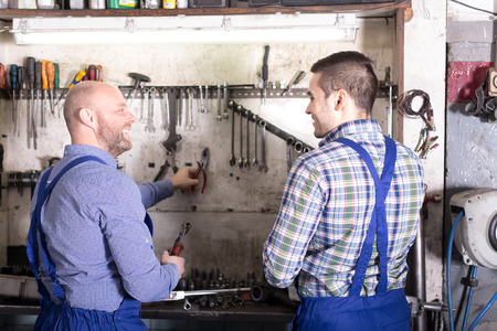 toiling: Two happy servicemen with tools in a repair shop
