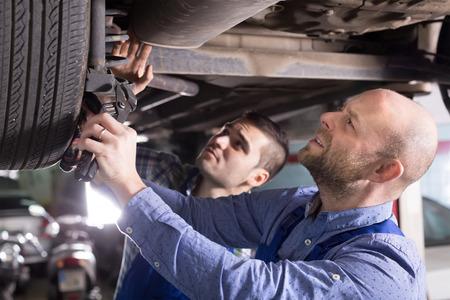 Twee professionele automonteurs controleren van de druk in de banden bij garage Stockfoto
