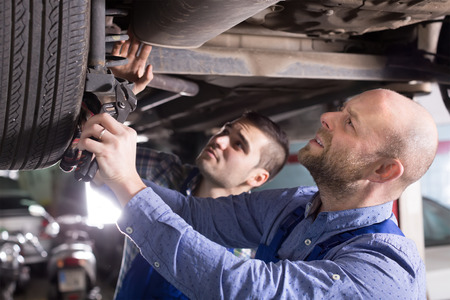 Two professional car mechanics checking up pressure in tires at garage