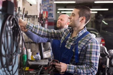 Portrait of two positive adult garage workmen near facilities photo
