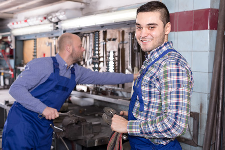 toiling: Portrait of two men working in a workshop Stock Photo