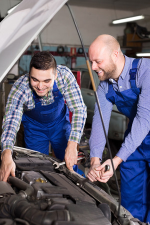 mounting holes: Cheerful male mounting specialists working at auto repair shop.