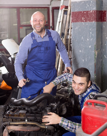 specialists: Smiling adult mounting specialists working at auto repair shop.