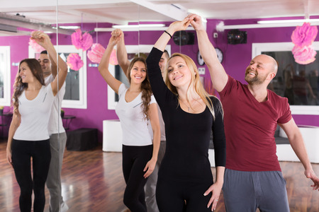 Group of joyful smiling young adults dancing salsa at dance class Stock Photo