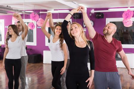 taniec: Grupa radosnych uśmiechniętych młodych ludzi tańczących salsę w klasie tanecznej Zdjęcie Seryjne