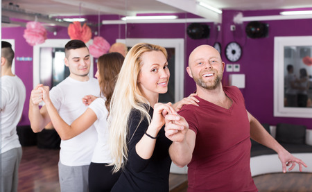 normal school: Group of happy smiling young adults dancing at dance class