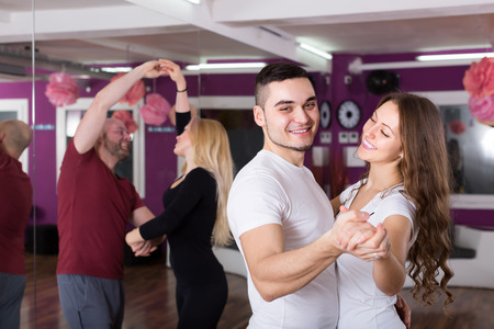 unprofessional: Group of smiling young adults dancing salsa in club