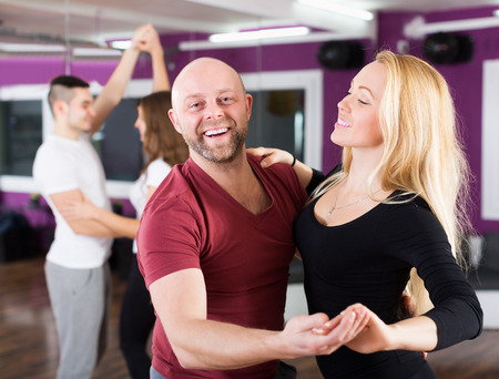 Couples enjoying of partner dance and smiling indoor