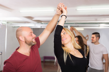 Smiling young couples enjoying of partner dance indoor Stock Photo
