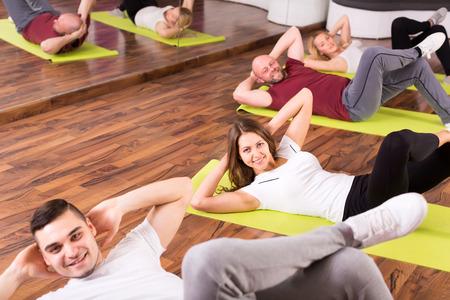 estudiantes adultos: Adultos sonrientes felices que hacen los ABS en un gimnasio bajo techo en un grupo