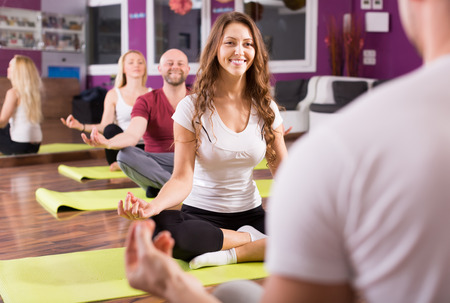 yoga man: Happy smiling young adults having yoga class in sport club Stock Photo