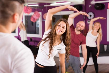 estudiantes adultos: Adultos felices que tienen un grupo de clases de fitness en el club de deporte