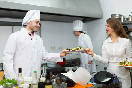 prepared food: Cook gives to positive waitress plates with prepared food