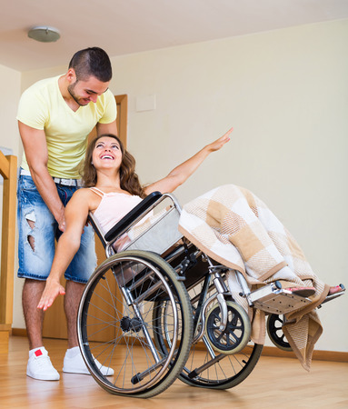 invalidity: Young caregiver and person in invalid chair laughing at home Stock Photo