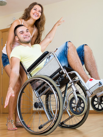 invalidity: Happy woman caregiver and young guy in a wheelchair Stock Photo