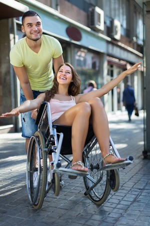 spouse: Husband taking happy young spouse on wheelchair in playful mood outside