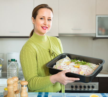 whitefish: Positive smiling housewife cooking filleted fish at kitchen